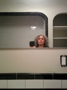 Esotouric's Kim Cooper takes a moment inside the remodeled bathroom where the young Bukowski was abused.