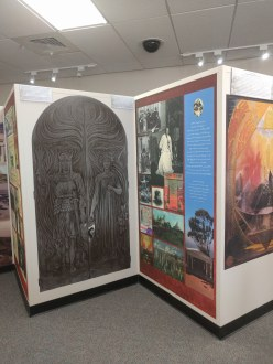 Two of ten wall panels introducing viewers to the exhibit 'Revisiting Visionary Utopia: Katherine Tingley's Lomaland, 1898-1942.' Panel on the left is an enlarged photograph of the huge doors, over twelve feet high, carved by Reginald Machell c.1901 for the entrance to the Aryan Temple (renamed the Temple of Peace after World War I).